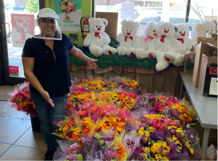 Romina Orozco-Encio with flower arrangements and gifts customers can buy or send to loved ones.